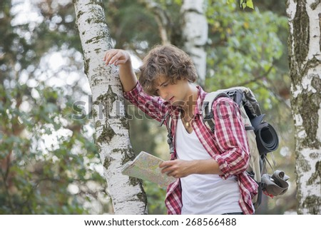Backpacker reading map while leaning on tree trunk in forest - stock photo