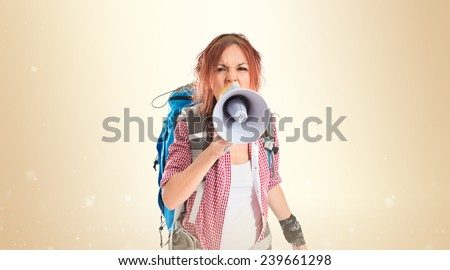 backpacker shouting by megaphone over ocher background - stock photo