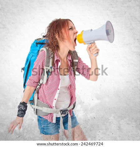 backpacker shouting by megaphone over textured background - stock photo