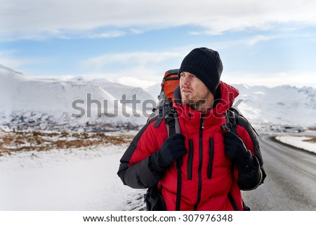 Backpacker traveling holiday on a budget walking along a empty road, in harsh winter snowy cold extreme conditions - stock photo