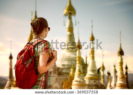 Backpacker traveling  with backpack and looks at Buddhist stupas. Myanmar - stock photo