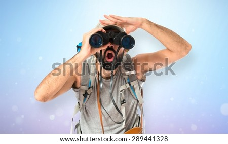 Backpacker with binoculars over shiny background - stock photo