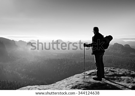 Backpacker with eyeglasses and poles in hand. Sunny spring daybreak in rocky mountains. Hiker with big backpack stand on rocky view point above misty valley. - stock photo