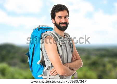 Backpacker with his arms crossed on unfocused background
