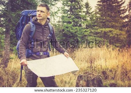 Backpacker with map to find directions in wilderness area. Filtered image:cross processed vintage effect.  - stock photo