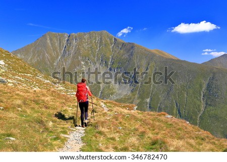 Backpacker woman departing on a sunny trail above the mountains - stock photo