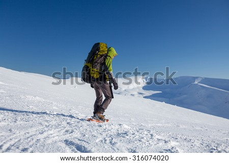 Backpacker woman is walking in winter mountains on sunny day