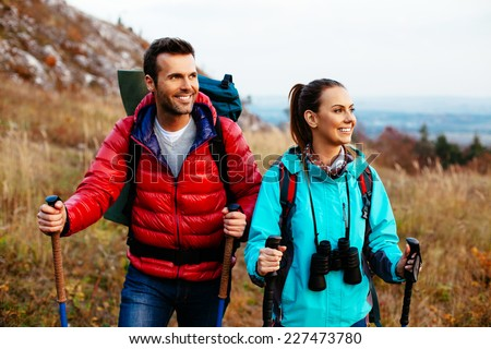 Backpackers couple hiking during fall with sticks - stock photo