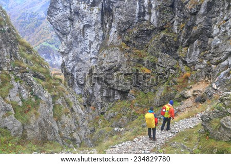 Backpackers descend a rocky trail in overcast day - stock photo