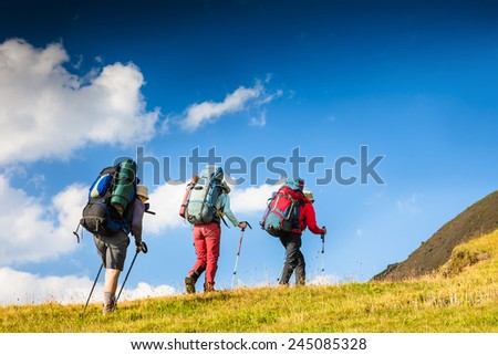 Backpackers hiking on the path in mountains on sunny day - stock photo