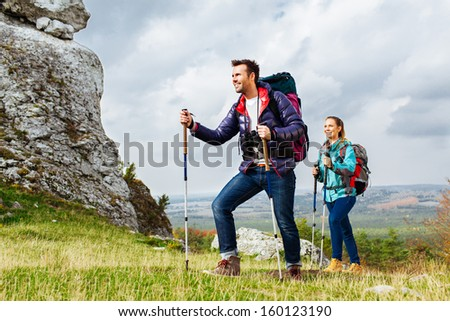 Backpackers hiking. Two young tourists on the trial - stock photo