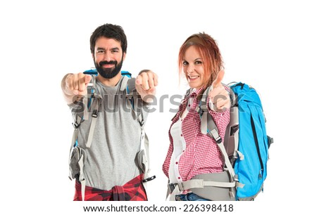 Backpackers making Ok sign over white background - stock photo