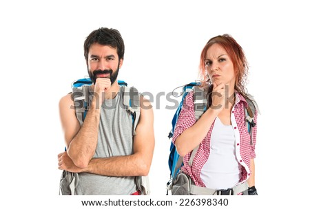 Backpackers thinking over isolated white background - stock photo