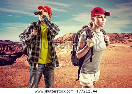 Backpacking people. Young trekking couple in the desert. Man hiker looking in binocular and female traveler with backpack over beautiful landscape background.  - stock photo