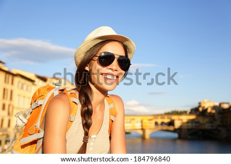 Backpacking women traveler on travel in Florence wearing sunglasses smiling happy by Ponte Vecchio during vacation holidays in Tuscany, Italy, Europe. - stock photo
