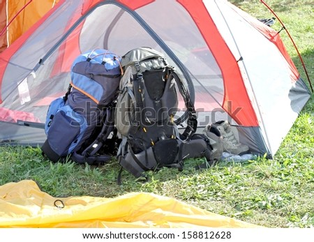backpacks of hikers resting above the tent during the adventurous ride - stock photo
