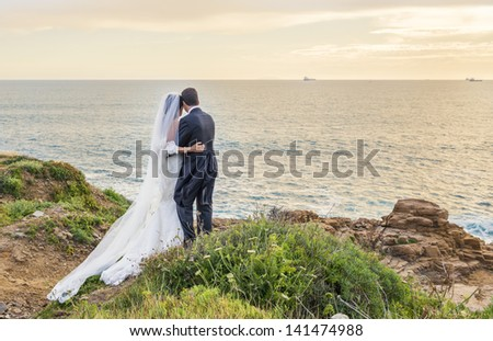 backs of bride and groom against landscape at dawn in italy - stock photo