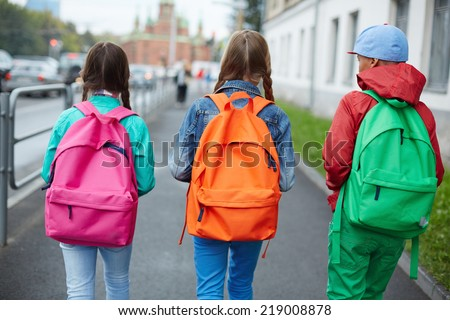 Backs of schoolkids with colorful rucksacks moving in the street - stock photo