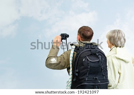 Backs of senior hikers with binoculars on trip