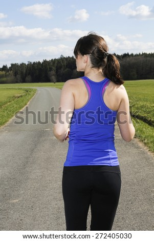 backside of a young woman jogging outdoors on the countryside - stock photo