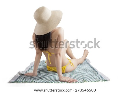 Backside of young female model wearing swimsuit and sitting in the studio with mat - stock photo