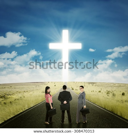 Backside view of entrepreneurs standing on the road with a cross on the end of the road
