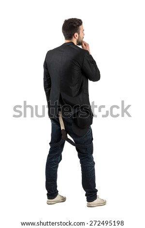 Backside view of young artist looking at blank white wall.  Full body length portrait isolated over white background.  - stock photo