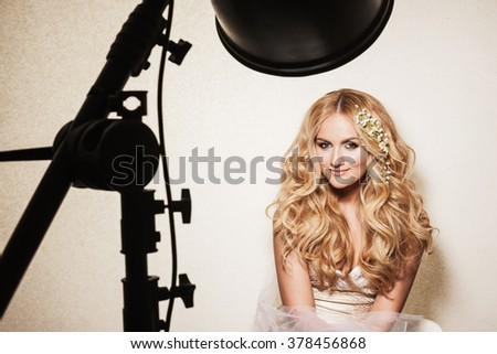 Backstage portrait of affectionate blond woman. Beautiful bride with wedding makeup, hairdo and wedding decorations.  - stock photo