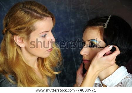 Backstage scene: esthetician doing model makeup. - stock photo