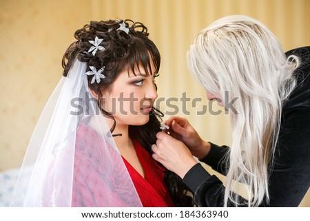 Backstage scene: Professional Make-up artist doing glamour model makeup at work  - stock photo
