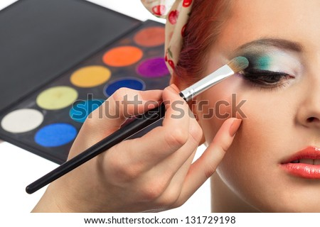 Backstage scene: Professional Make-up artist doing pinup model makeup at work - stock photo