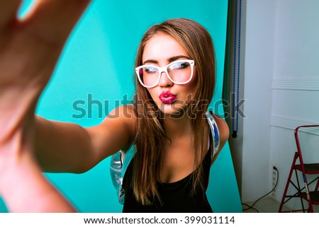 Backstage studio portrait of beauty woman making selfie at shooting. bright stylish outfit, duck face, photoshoot. - stock photo