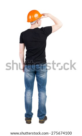 Backview an engineer in construction helmet stands. Rear view people collection.  backside view person.  Isolated over white background. He puts his hand to his eyes a man protects his eyes from sun. - stock photo