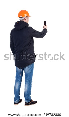 Backview of an engineer in construction helmet stands and using a mobile phone. Standing young guy. Rear view people collection.  backside view of person.  Isolated over white background. - stock photo