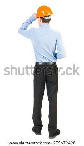 Backview of an engineer in construction helmet stands. Standing young guy. Isolated over white background. The man in trousers and shirt standing at a construction site holding hand helmet. - stock photo