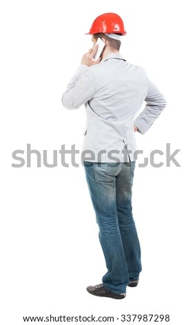 Backview of business man in construction helmet stands and enjoys tablet or using a mobile phone. Standing young guy. Rear view people collection.  backside view of person. - stock photo