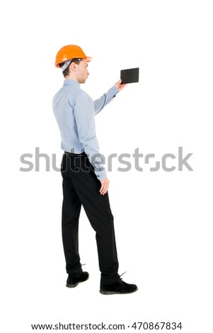 Backview of business man in construction helmet stands and enjoys tablet or using a mobile phone. Standing young guy. Rear view people collection.  backside view of person.  Isolated over white