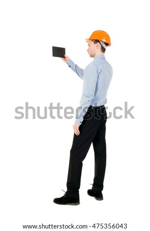 Backview of business man in construction helmet stands and enjoys tablet or using a mobile phone. Isolated over white. Curly businessman in a light jacket and a helmet shoots video on the tablet.