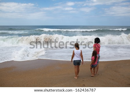 Backview of mother with two daughters looking over ocean on sandy beach
