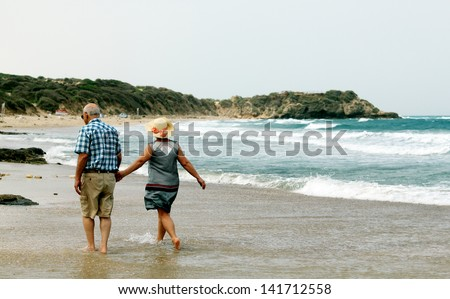 backview of senior couple walking on sandy beach - stock photo