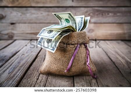 backwards money in burlap sack on wooden background - stock photo