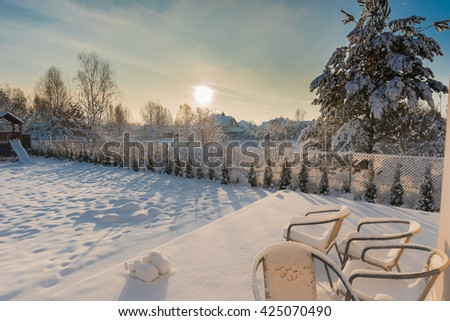 Backyard covered with snow on a sunny winter morning - stock photo