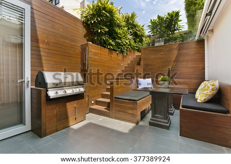Backyard cozy patio area with wicker furniture set - stock photo