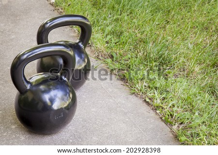 backyard fitness concept - a couple of heavy iron kettlebells on a sidewalk