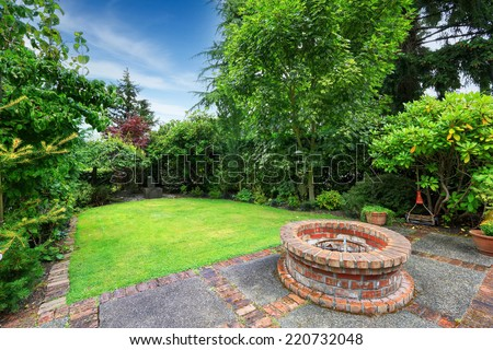 Backyard landscape. patio area with brick fire pit - stock photo