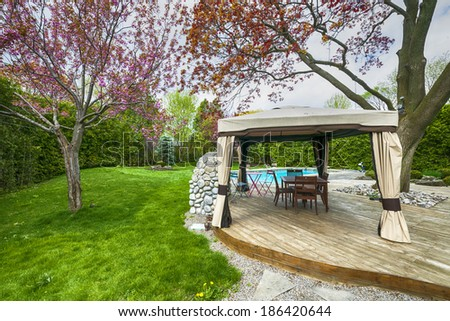 Backyard of residential house in spring with wooden deck and gazebo - stock photo