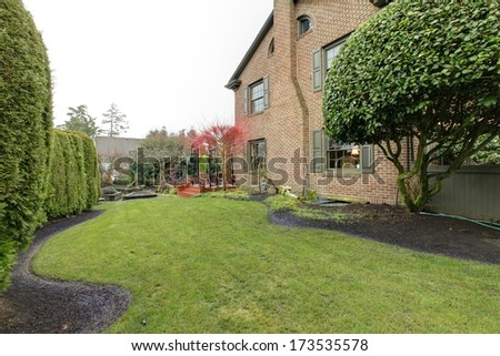 Backyard of stoned classic house with green trim , red tree and hedge - stock photo