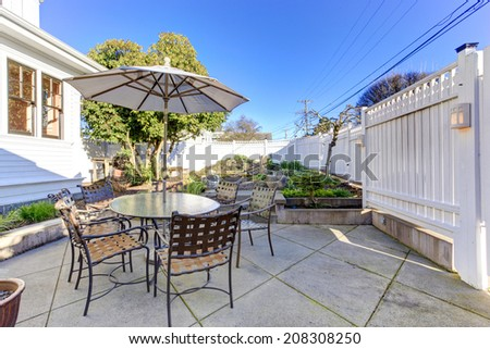 Backyard patio area with table, chairs and umbrella - stock photo