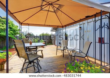 Backyard Patio Area With Table Set And Opened Orange Umbrella. Northwest,  USA