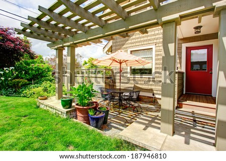 Backyard porch with red door and attached pergola. View of table set with umbrella - stock photo